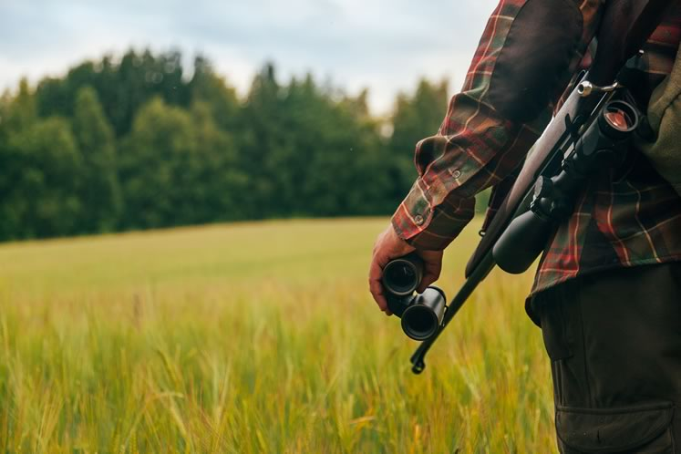 A hunter takes to the field with a 12-gauge pump-action shotgun. Photo by Visualspace | istockphoto.