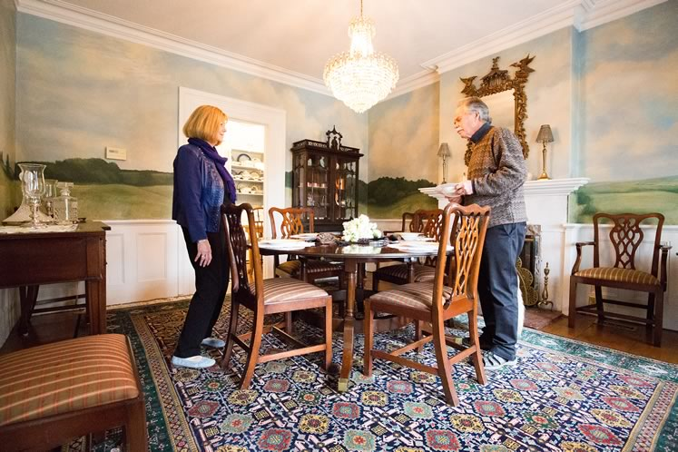 Gary and Mary in their dining room. The walls are covered in an ethereal mural of the surrounding landscape painted by Saskia Post. Photo by Erin Fitzgibbon.
