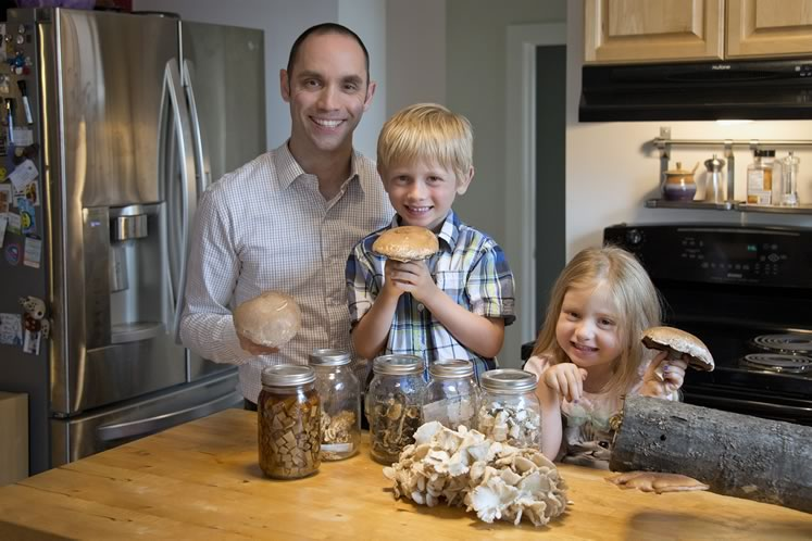 Kevin McAuslan in his Orangeville kitchen with Tenzin, 6, Violet, 4, and a bounty of mushrooms. Along with the portobellos ( Agaricus bisporus ) they're holding and the pile of oyster mushrooms ( Pleurotus ostreatus ), in the jars of dried fungi (left to right) are a tincture of birch polypore ( Fomitopsis betulina ), coral fungi from Hockley ( Hericium coralloides ), honey mushroom ( Armillaria mellea ), flowery blewit ( Lepista irina ) from Alton, and cubes of more birch polypore. On the oak log is a shiitake mushroom ( Lentinula edodes ) Kevin grew in his garden. Photo by Pete Paterson.