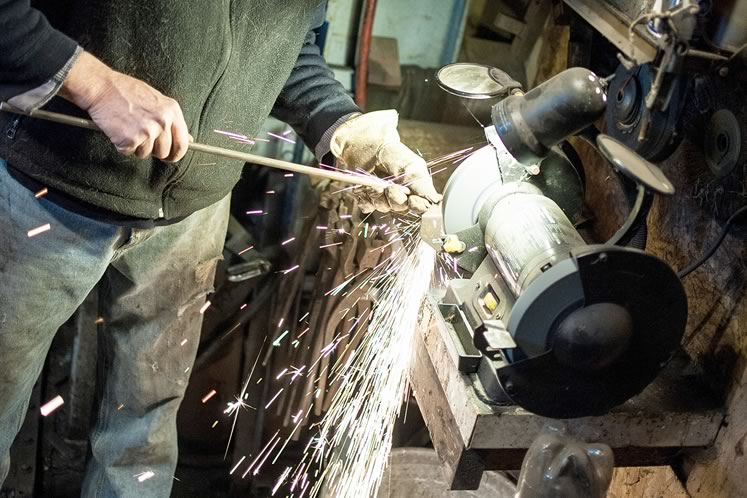 At Wareham Forge he grinds metal and works a piece of steel on his anvil, using the horn, the flat and the back of the anvil as pressure points. Photo by James MacDonald.