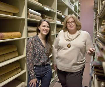 "Curator Sarah Robinson (left) and archivist Laura Camilleri between the rolling shelves that house historic documents in the Museum of Dufferin. Laura and Sarah encourage people to talk to them about possible museum donations. ""It's the stories that help us decide what's vital,"" says Sarah. Photo by Pete Paterson."