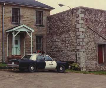 The walls of the Dufferin jail's outdoor yard were built with an inward slant to prevent prisoners from scaling them. The slant can be seen in this exterior photo taken in 1986 after the jail was closed to be renovated to house municipal offices. De Ha Josef for the County of Dufferin.