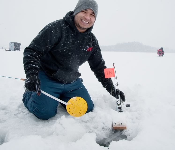 Gregory Chang-Kee uses a plastic ladle to scoop slush from his ice hole. Photo by Rosemary Hasner / Black Dog Creative Arts.