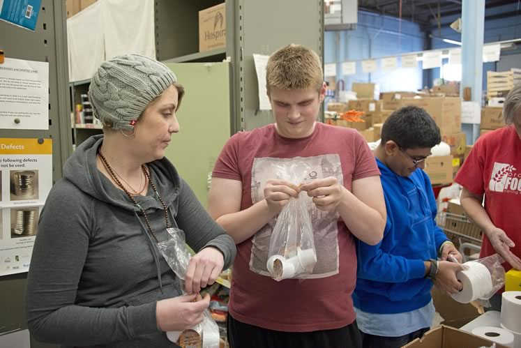 Active Lives program director Kim Van Ryn works with participant Michael during their regular volunteer stint at the Orangeville Food Bank. Photo by Pete Paterson.