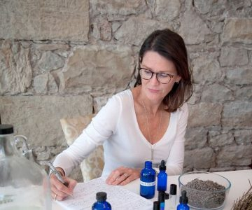 Lee Anne Downey sits at her kitchen counter with the lavender oil she pressed last summer at Stonewell Farm. She is developing ideas for a small-batch line of lavender products to debut this year. Photo by Rosemary Hasner / Black Dog Creative Arts.