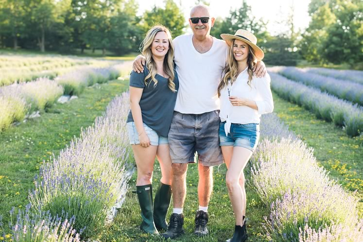 At their family farm near Creemore, Emma Greasley, left, and Jessica Ridding flank their father, Brian Greasley, between rows of lavender. Photo by Jessica Crandlemire, Light and Shadow Photography.