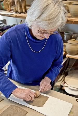 Mary Lazier creates one of her slab pottery bowls at her Mulmur studio. The intricate patterning is achieved using molds of vintage lace and wooden texture rollers. The bowl will be glazed in bluish white. Photo by Pete Paterson.