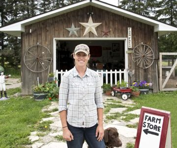 Rockcliffe Farm owner Alix Bezak in front of her on-farm shop with her chocolate lab, Goose. Photo by Pete Paterson.