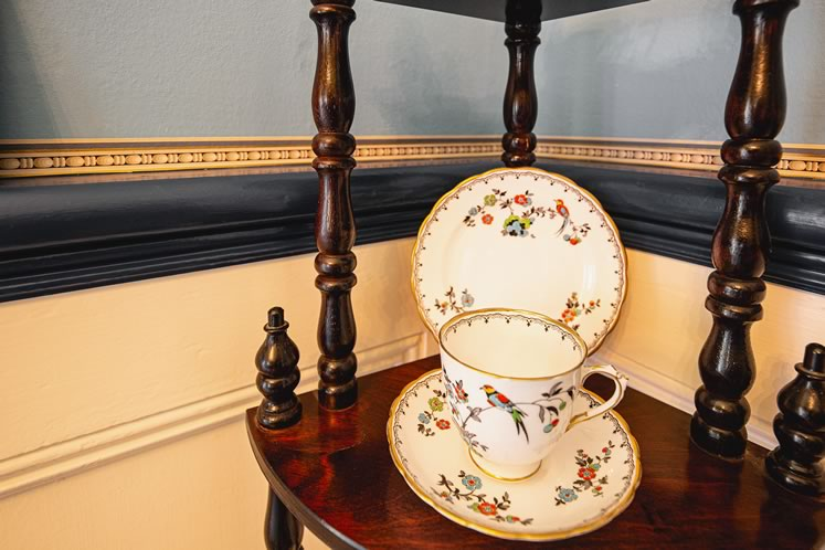 Fragments of the previous owners' wallpaper have been preserved. The pattern is almost identical to a tea set displayed nearby. Photo by Erin Fitzgibbon.