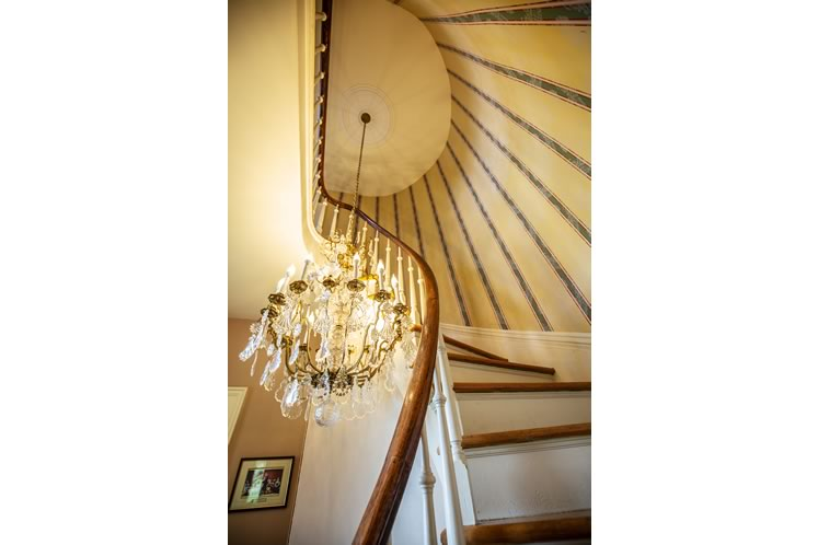 A stunning 1850 Louis XV-style chandelier hangs above the curved central staircase. Photo by Erin Fitzgibbon.