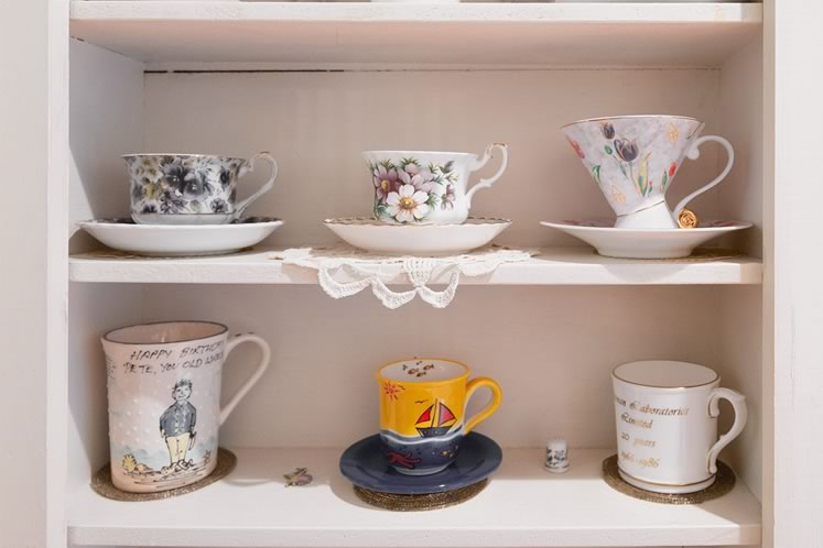 Sandy Reeves' eclectic vintage china is tucked into a hallway cabinet. Photo by Erin Fitzgibbon.