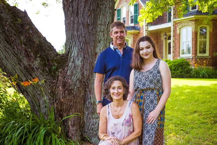 Sandy and Peter Reeves with Olivia, one of their daughters. The family moved to this grand Victorian farmhouse in 2016. Photo by Erin Fitzgibbon.