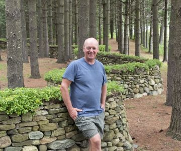 Dry stone waller Eric Landman stands on a private Caledon property where he has completed many walls and structures. Photo by Pete Paterson.