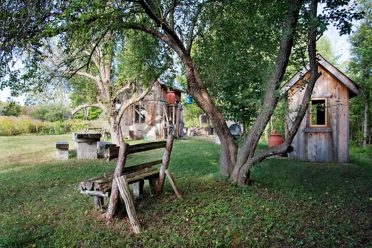 An outdoor kitchen, pizza oven, outhouse and sturdy wooden furniture expand John Farrugia's living space. Photo by Rosemary Hasner / Black Dog Creative Arts.