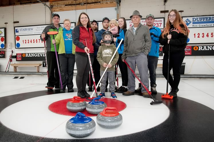 The Hulse family, Orangeville's curling dynasty (l–r): Jeff Hulse, Kathy Stranks, Barb Hulse, Nathan Hulse, AJ Hulse holding his daughter Zoey, Cathryn Madden, Jim Hulse, Tyler Hulse, McKenna Hulse, and young Bentley Hulse-Brown in the foreground. Photo by Rosemary Hasner / Black Dog Creative Arts.