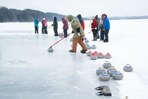 Curlers prepare to compete on a brisk February day at the pond spiel on Island Lake. Photo by Rosemary Hasner / Black Dog Creative Arts.