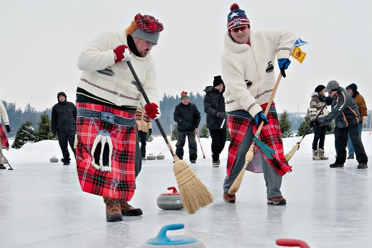 Jason and Collin Cook's brooms may not have much effect on the hard natural ice, but they add to the fun. Photo by Rosemary Hasner / Black Dog Creative Arts.