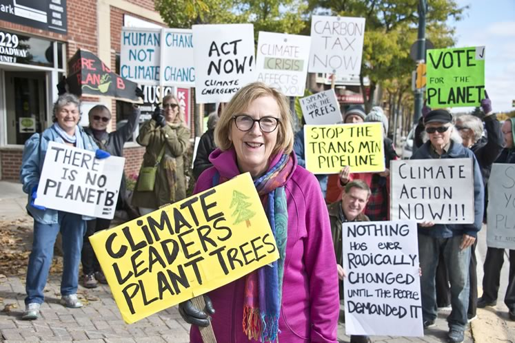 Activist Nancy Urekar has hoisted a sign and marched along Broadway in Orangeville every Friday at noon since January. Photo by Pete Paterson.
