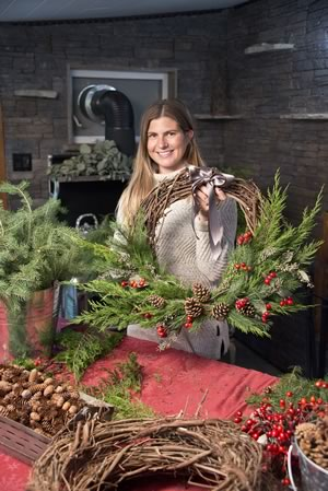Florist Jessica Giovanatto holds one of the rustic, handmade Christmas wreaths she makes in her year-round workshop – the closed-in porch at the Caledon farm where she grew up. Photo by Pete Paterson.