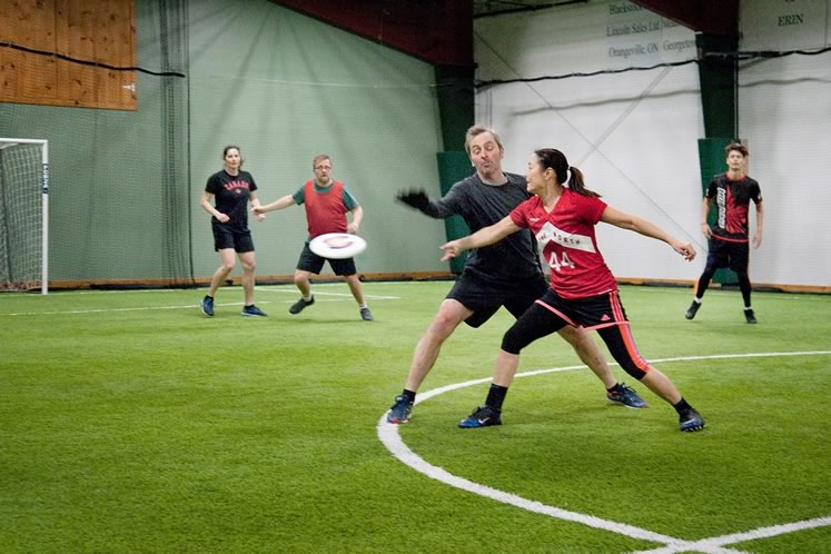 Ultimate champion Monica Kerr-Coster defends against an opponent at a recent indoor pickup game in Erin. Photo by Rosemary Hasner / Black Dog Creative Arts.