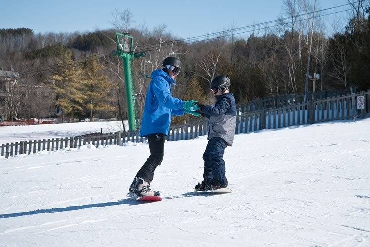 Snowboard instructor Fred Welsh offers guidance to young novice Jayden Mattia.Photo by Rosemary Hasner / Black Dog Creative Arts.