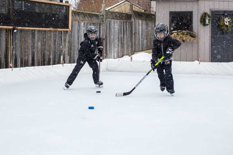 Zander and Nixon Alphonso hit the ice in the backyard of their Orangeville home. Photo by Erin Fitzgibbon.