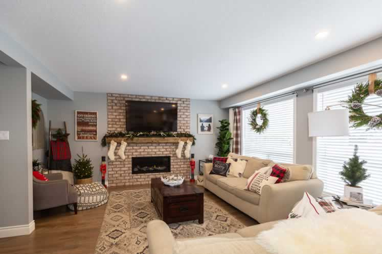 The cozy family room is dressed for the holidays in greenery and seasonal decor. Photo by Erin Fitzgibbon.