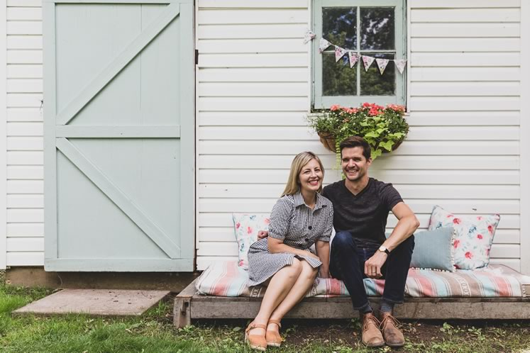 Julia and Dave Grys sit on a homemade bench in front of their refurbished potting shed. Photo by Erin Fitzgibbon.