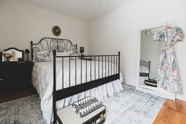 A wrought-iron bed adds romance to the principal bedroom. Photo by Erin Fitzgibbon.