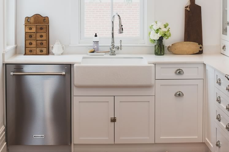 The newly renovated kitchen pops with white cupboards and polished nickel hardware. Photo by Erin Fitzgibbon.