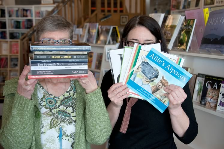BookLore staffers Brenda Juno and Jan Hettwer peek out from behind a bumper crop of new local books. Photo by Pete Paterson.