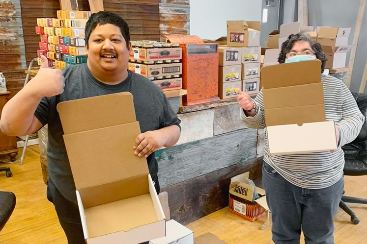 At The Birch Shoppe in Palgrave, Adam Ali (left) and Joshua Newton of the White Birch Special Needs Day Program create gift boxes filled with local pantry products.