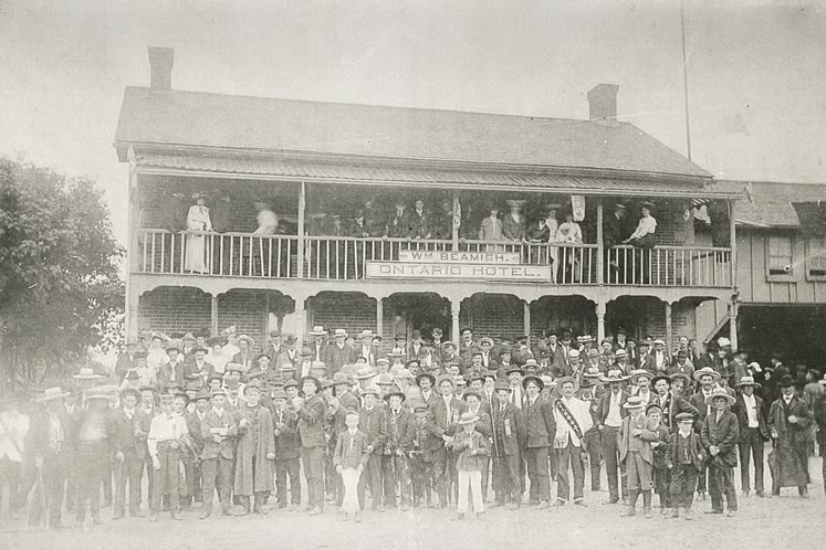 Huge crowds filled every community on Orangemen's Day. In Caledon East, c.1900, the Ontario Hotel had to install extra balcony supports for this group photo. Photo courtesy Doris Porter.