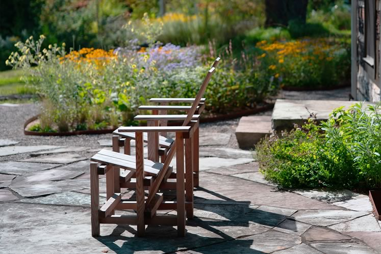 Wave Hill chairs welcome visitors to the sandstone terrace. The Ovals beyond are freshly planted with pollinator-friendly perennials with a massive black cherry overhead. Photo by Tony Spencer.