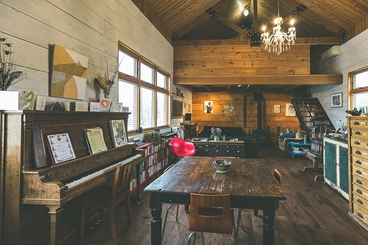 The barn-style home centres on a main living area with 20-foot ceilings and filled with collectibles including salvaged specimen cabinets, at right, original to the Royal Ontario Museum. Photo by Erin Fitzgibbon.
