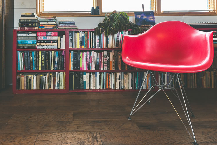 A red, moulded, mid-century modern chair adds a jolt of colour to the rustic space. Photo by Erin Fitzgibbon.