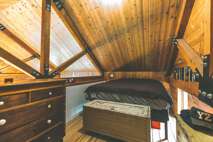 Sara and Peter's cozy bedroom is tucked into a loft space. Photo by Erin Fitzgibbon.