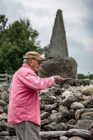 Joe Burchell uses a dowsing rod to commune with the energy of the Earth. Photo by Kerry Knudsen.