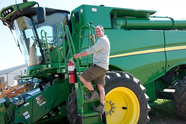Grain farmer Darryl Burnett climbs aboard a massive John Deere harvester at his farm in East Garafraxa. Photo by Pete Paterson.