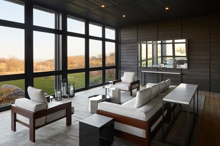 In the screened-in porch the seating and ceramic tables facing the wall of windows are by Minotti. Photo by Ben Rahn.