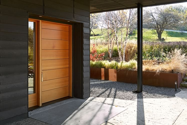 The home's simple covered entryway frames a view of the gardens to the west of the building. Photo by Ben Rahn.