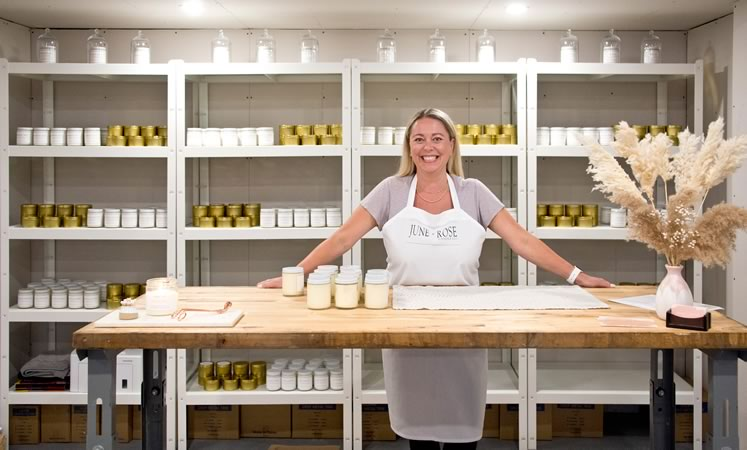 Candlemaker Melissa Lester in her pristine Caledon studio backed by tidy shelves of her handmade June + Rose Candle Co. products. Photo by Pete Paterson.