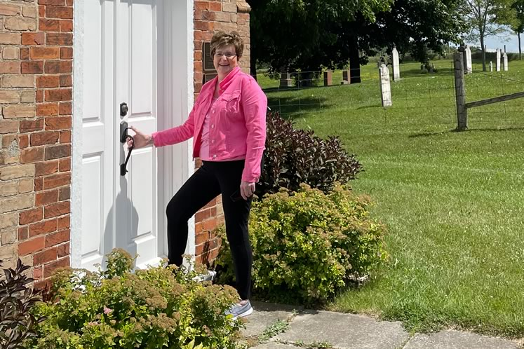 """Donna Holmes at the door of the Mono pioneer church that has been part of her life for as long as she can remember. """"It's where real life happens,"""" she says. Photo by Brenda Holmes."""